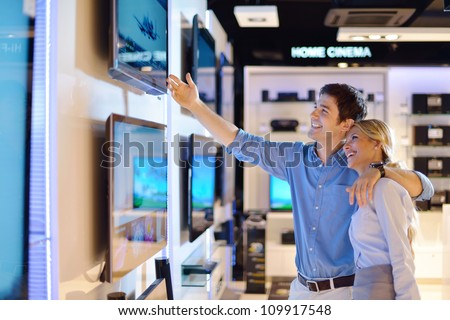 Young couple in consumer electronics store looking at latest laptop, television and photo camera - stock photo