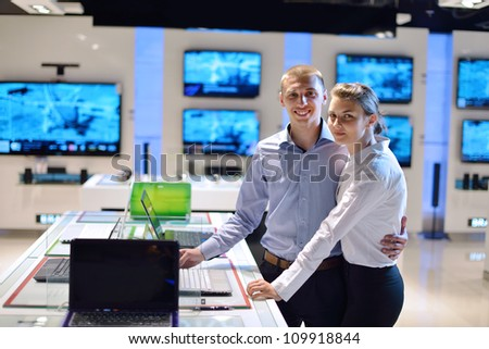 Young couple in consumer electronics store looking at latest laptop, television and photo camera to buy - stock photo