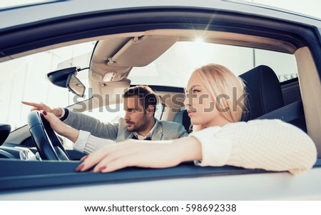 Young couple in convertible car enjoying day trip.