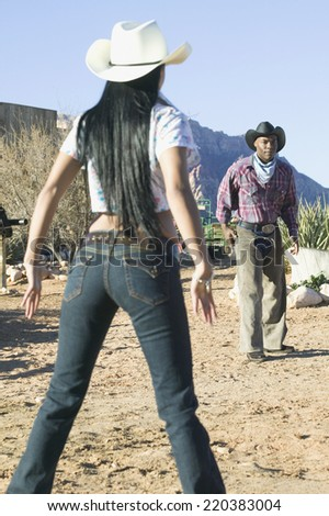 Young couple in cowboy outfits having a shootout - stock photo