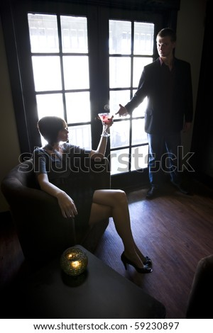 Young couple in dark room, woman holding drink