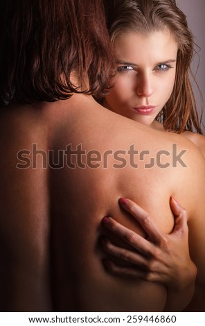 Young couple in each other's arms on a dark background