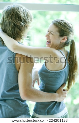 Young couple in exercise clothing standing with arms around each other, woman laughing - stock photo