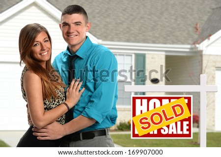 Young couple in front of newly purchased home - stock photo
