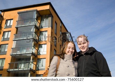 Young couple in front of their new home - stock photo