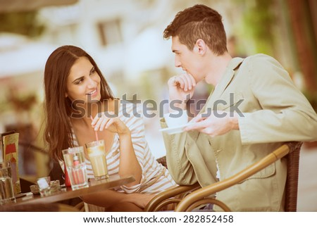Young couple in garden cafe flirts and enjoys the coffee. - stock photo