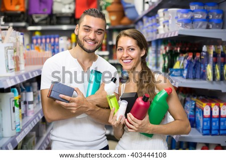 Young couple in good spirits with detergents, shampoo and perfume  in the store