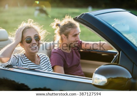 Young couple in his convertible car, happy to drive on a country road, focus on the woman. Shot with flare.There are some blurred cows at the background - stock photo