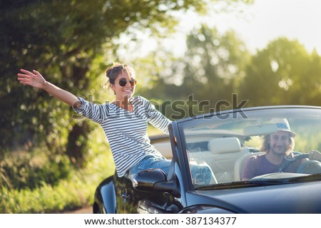 Young couple in his convertible car, happy to drive on a country road in summer.Shot with flare
