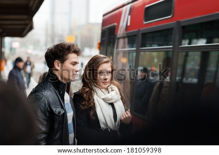 Young couple in jackets standing at railway station - stock photo