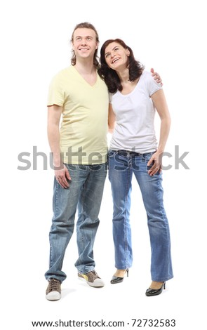Young couple in jeans, boy and girl, are standing in embrace and looking up - stock photo