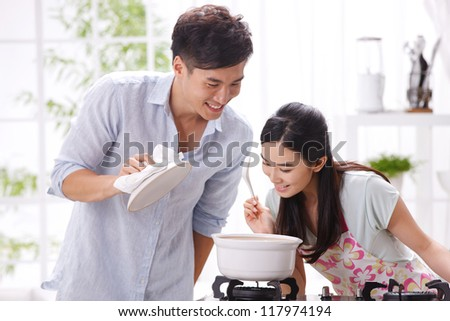 Young couple in kitchen - stock photo