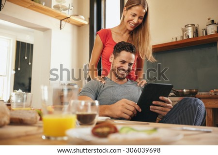 Young couple in kitchen looking at tablet pc smiling. Woman standing by her boyfriend sitting using digital tablet in morning. - stock photo