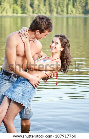 Young couple in lake water lost in love - stock photo