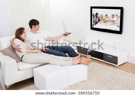 Young Couple In Livingroom Sitting On Couch Watching Television