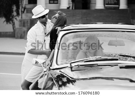 Young couple in love and jealous girl in retro car - stock photo