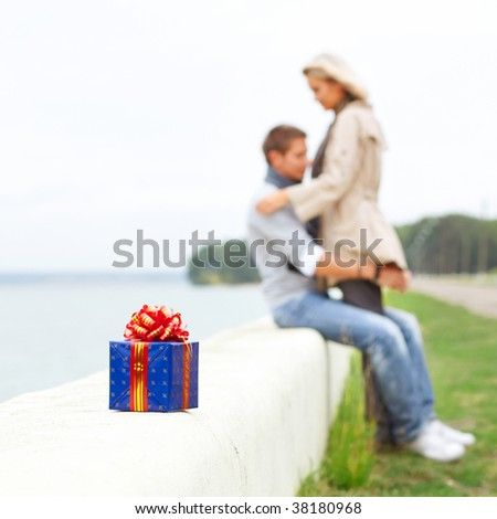 Young couple in love are on the beach. With giftbox in front. - stock photo