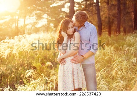 young couple in love at sunset in the field - stock photo