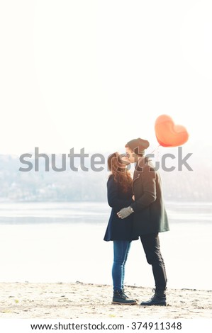 Young couple in love, at the riverside, with a red balloon, kissing - stock photo
