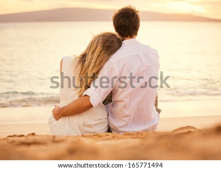 Young couple in love, Attractive man and woman enjoying romantic evening on the beach watching the sunset - stock photo