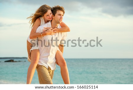 Young couple in love, Attractive man and woman enjoying romantic evening walk on the beach,  Watching the sunset - stock photo