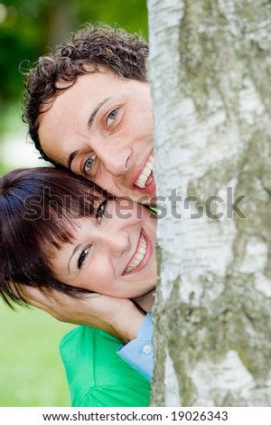 Young couple in love behind a tree (birch) - stock photo