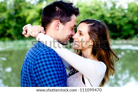 Young couple in love by the pond. Selective focus. - stock photo