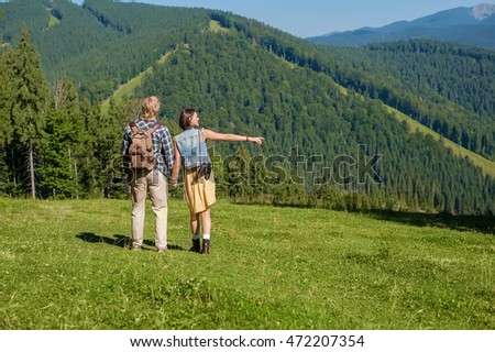 young couple in love dressed in country style holding hands and walking on mountain high
