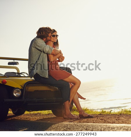 Young couple in love embracing and kissing. Young man and woman sitting on their car hood. Romantic young couple on road trip.