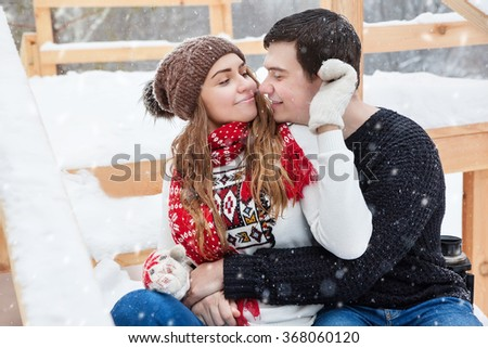 young couple in love enjoying a walk in winter park - stock photo