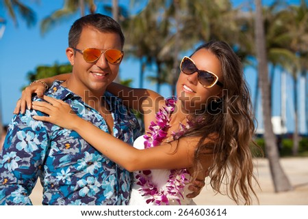 Young couple in love feeling happy on the Hawaiian beach, Oahu, Hawaii, USA. Vacations And Tourism Concept. Summer luxury vacation in Hawaii. - stock photo