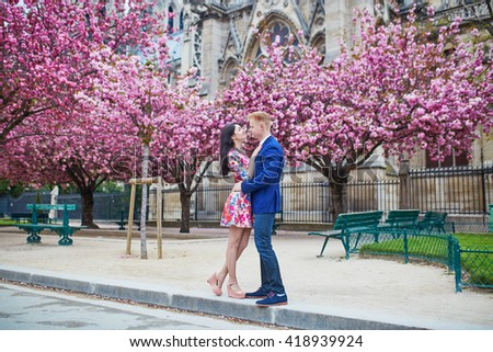 Young couple in love having a date under pink cherry blossom trees, Notre-Dame cathedral in the background. Tourists visiting Paris at spring