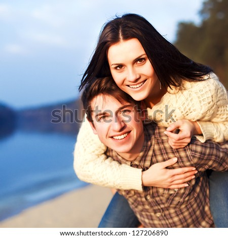 Young couple in love having fun, laughing and smiling outdoor. Spring sunny portrait - stock photo