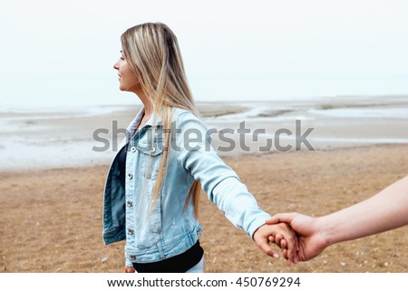 Young couple in love holding hands are walking by the beach against seashore in mist. Happy young family. Travel and vacation concept. - stock photo