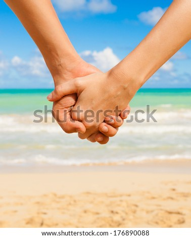 Young couple in love holding hands by the beach.