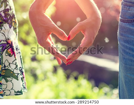 Young couple in love holding hands in the sunset in summer evening. Bright toning picture - stock photo