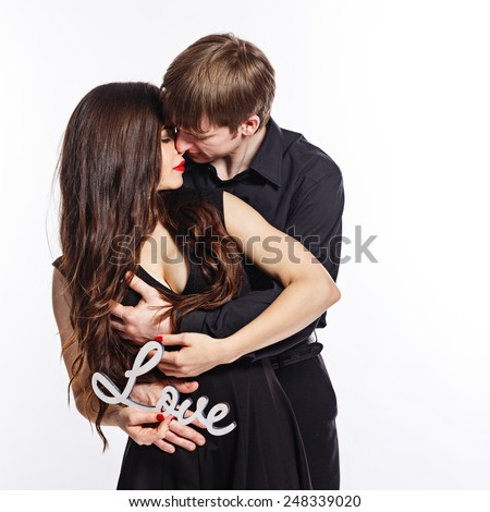 Young couple in love hugging each other. Are holding an inscription love - stock photo