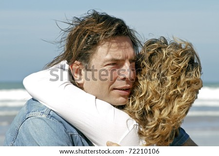 Young couple in love hugging each other at the beach