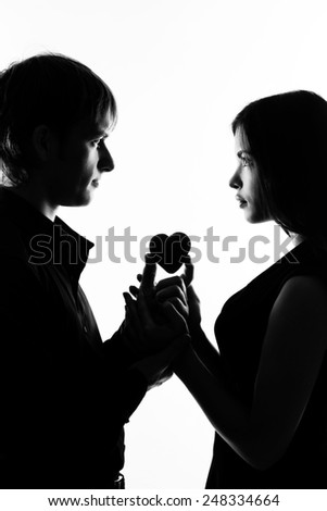 Young couple in love hugging each other, black and white photo. Are holding heart - stock photo