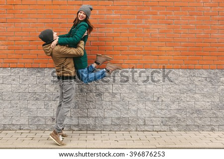 young couple in love, hugging, smiling.  Women in motion, jump. Outdoors. Brick background. copyspace