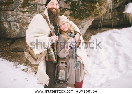 Young couple in love in rustic style in the winter woods with a blanket - stock photo