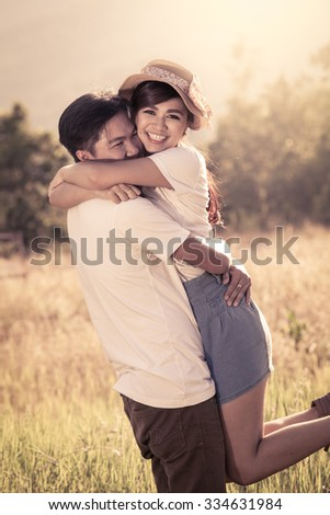 Young couple in love  in the meadow in vintage color filter - stock photo