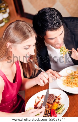 Young couple in love is enjoying a romantic dinner, he has some noodles while she is eating a good steak - stock photo