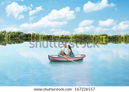 young couple in Love kisses on boat on lake