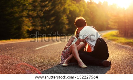 Young couple in love kissing on the road in summer evening - stock photo