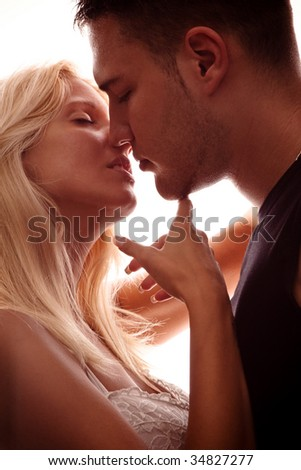 young couple in love, kissing, studio shot, back light