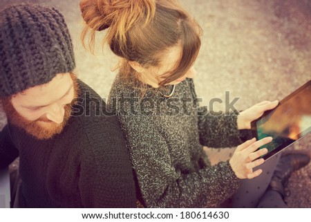 young couple in love lifestyle outdoor using tablet at the park - stock photo