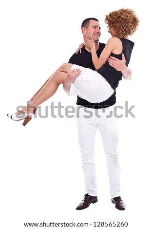 Young couple in love, man holding his beloved in his arms, they are smiling and looking at each other