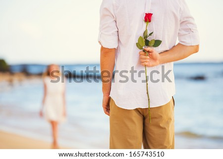 Young Couple in Love, Man holding surprise rose for beautiful young woman, Romantic Date - stock photo