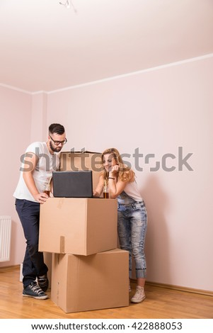 Young couple in love moving in a new apartment, standing next to cardboard boxes, looking at a laptop computer and surfing the web while planning to redecorate their new home